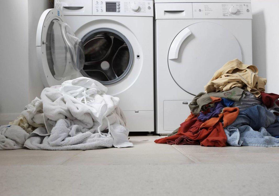 Две горки белья у стиральных машин