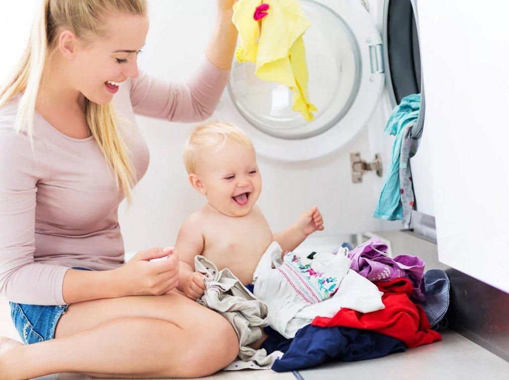 Молодая мама с ребёнком у стиральной машины