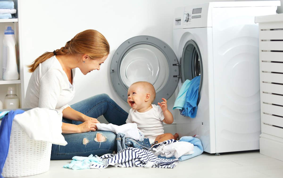 Девушка с ребёнком сидит у стиральной машины