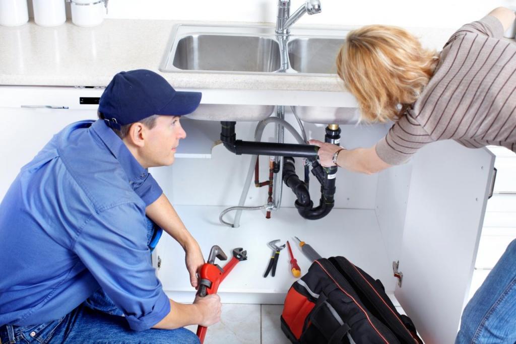Мастер ремонтирует трубы на кухне