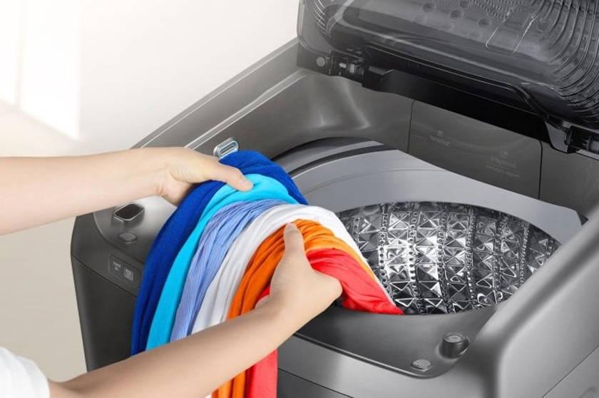 Достаёт бельё из стиральной машины